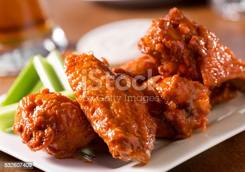 A plate of buffalo style chicken wings with celery and blue cheese with a beer on a bar or restaurant table.  Please see my portfolio for other food and drink images.