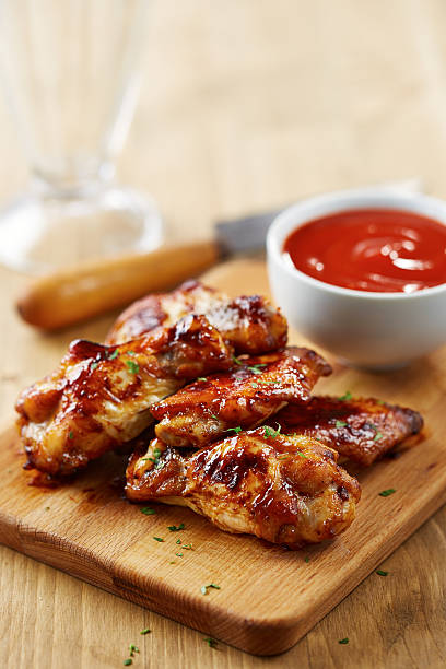 Chicken wings with sriracha sauce Chicken wings with sriracha sauce on wooden table sriracha tiger zoo stock pictures, royalty-free photos & images