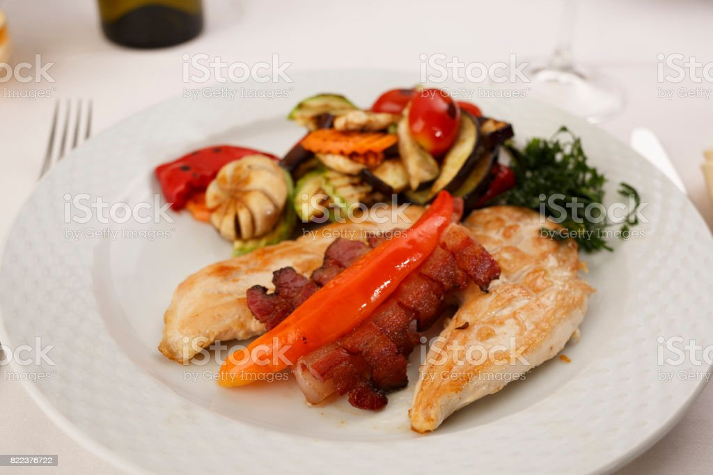 Chicken with bacon and grilled vegetables arranged on a plate,...