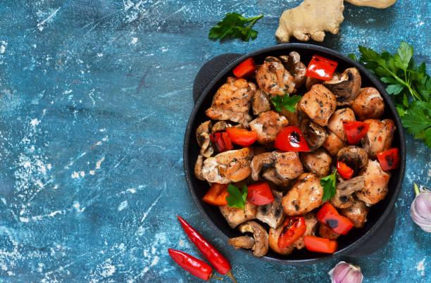 huhn mit pilzen und paprika auf einem blauen hintergrund konkreter! - pilzpfanne stock-fotos und bilder