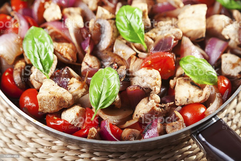 Chicken with onion and cherry tomatos royalty-free stock photo