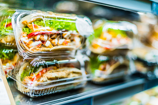 Chilli chicken with pita, pre-packaged sandwiches displayed in a commercial refrigerator