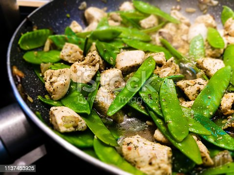 Chicken with snow peas on the pan - close up photo