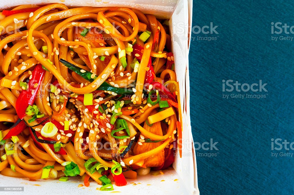 Chicken wok in paper box on a blue background royalty-free stock photo