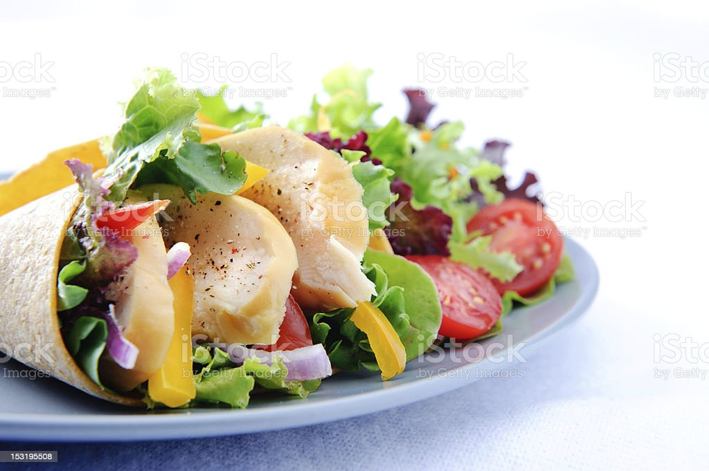 Chicken wrap on plate with side salad stock photo