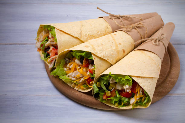 Chicken wraps. Tortilla, burritos, sandwiches twisted rolls on wooden table. View from above, top stock photo