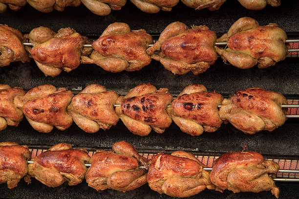Chickens on the rotisserie Succulent roasting chickens on a rotisserie at a market spit roasted stock pictures, royalty-free photos & images