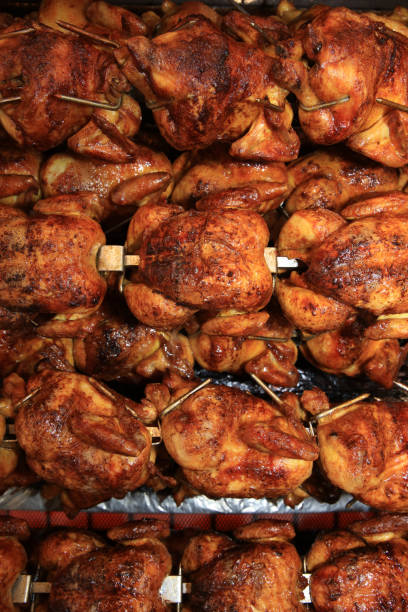 chickens roasting in rotisserie in germany. europe - girarrosto foto e immagini stock