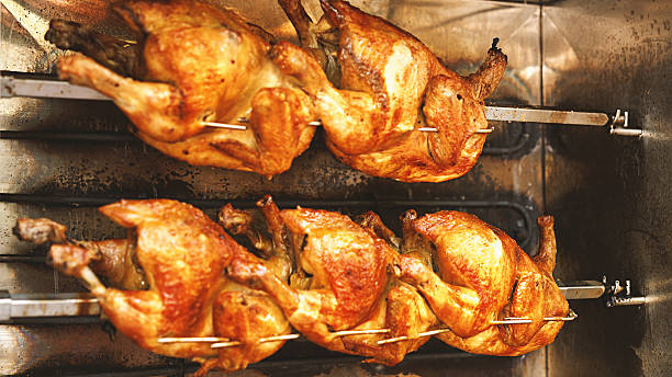 Chickens roasting in rotisserie. Closeup of five chicken spining in a rotisserie. Thay are minutes from being ready to serve. spit roasted stock pictures, royalty-free photos & images
