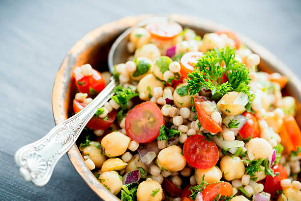 Chickpea and Couscous Salad A chickpea and pearl couscous salad mixed with tomatoes, onions and herbs. chick pea stock pictures, royalty-free photos & images