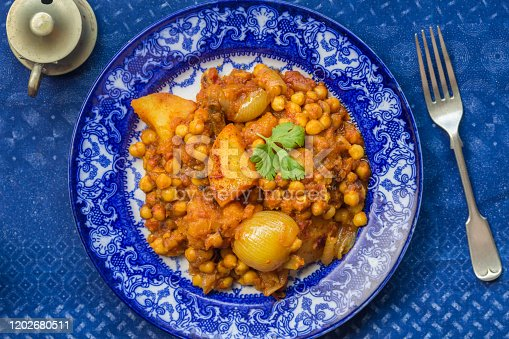 Chickpea and vegetable curry on blue and white plate - top view photo