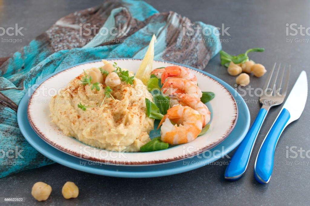 Puree van kikkererwten met room en boter geserveerd met gekookte garnalen op een witte en blauwe plaat op een grijze abstracte achtergrond. Gezonde voeding. Gezond eten concept royalty free stockfoto