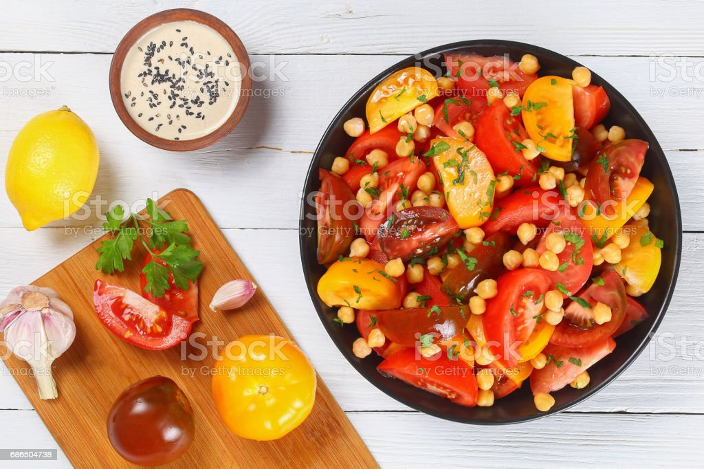 Kikärt tomater sallad i svart skål royaltyfri bildbanksbilder