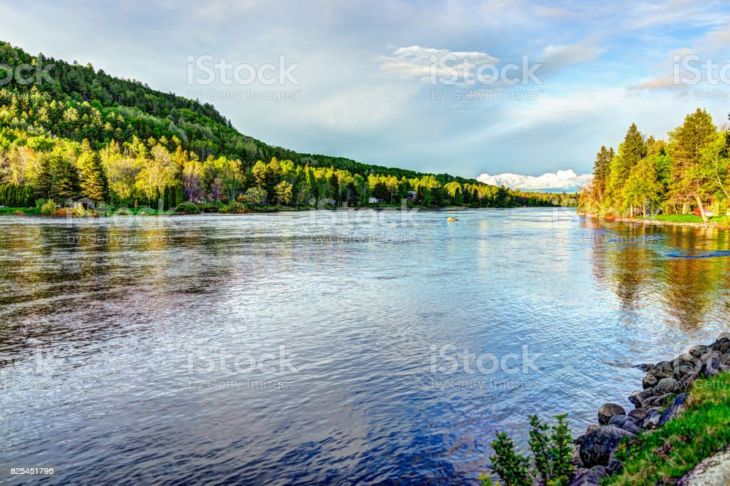 Chicoutimi river in Saguenay, Quebec, Canada with riverfront houses and forest during sunset stock photo
