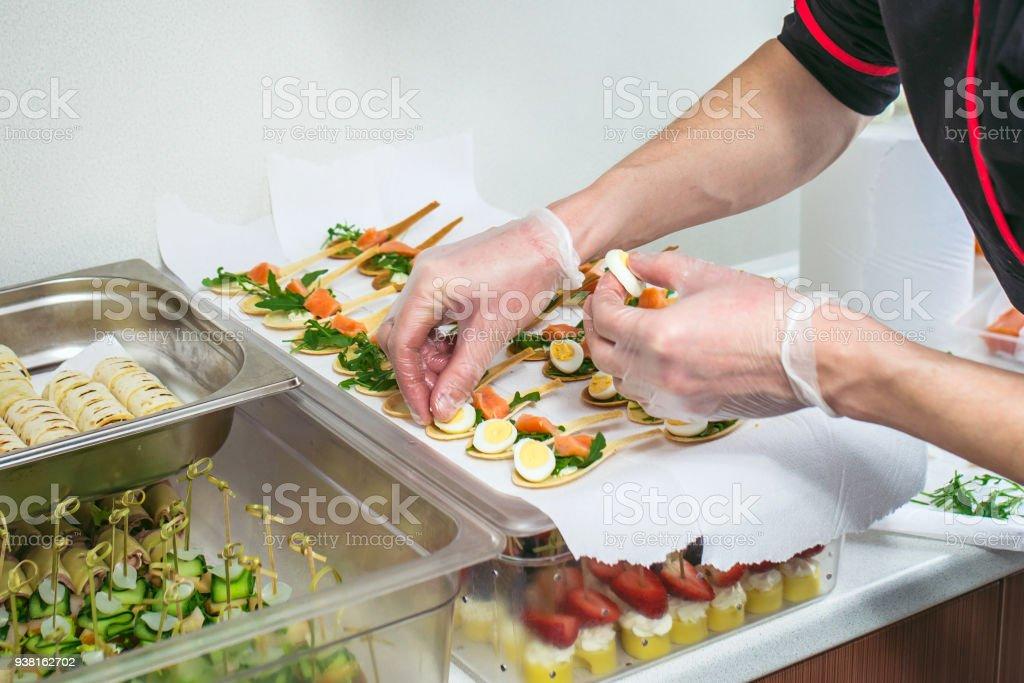 Jefe de cocina preparemos delicates, aperitivos. Servicio de catering. Reportaje de primer plano de manos. - foto de stock