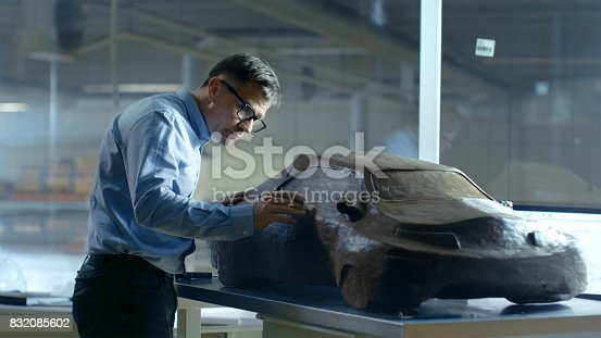 istock Chief Automotive Designer with Rake Sculpts Futuristic  Car Model from Plasticine Clay. He Works in a Special Studio Located In a Large Car Factory. 832085602