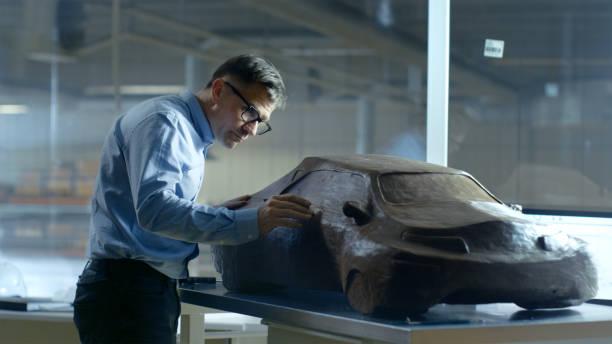 kfz chefdesigner mit rechen formt futuristisches automodell aus plastilin ton. er arbeitet in einem speziellen studio befindet sich in einem großen automobilwerk. - skulpturprojekte stock-fotos und bilder