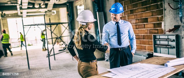 istock Chief constructor and female architect shaking hands on construction site 645971258