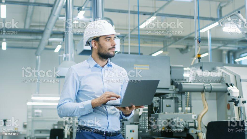 Chefingenieur im harten Hut geht durch moderne Lichtfabrik gedrückter Laptop. Erfolgreiche, schöner Mann in modernen industriellen Umfeld. – Foto