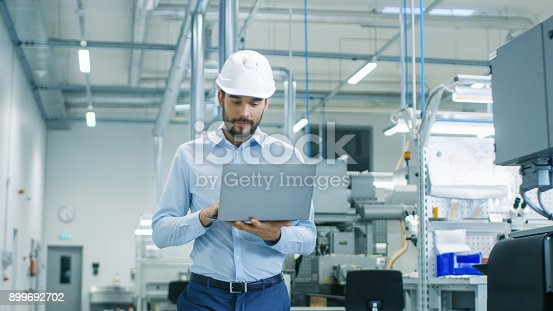 istock Chief Engineer in the Hard Hat Walks Through Light Modern Factory While Holding Laptop. Successful, Handsome Man in Modern Industrial Environment. 899692702