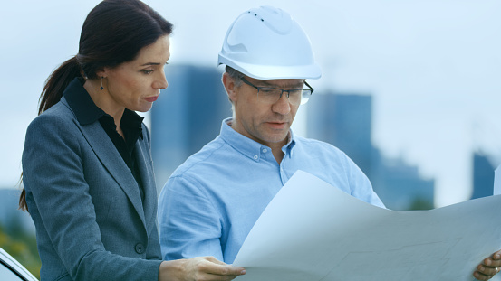 Chief Engineer Shows Project Drafts To Business Woman Investor. In the Background City with Skyscrapers.