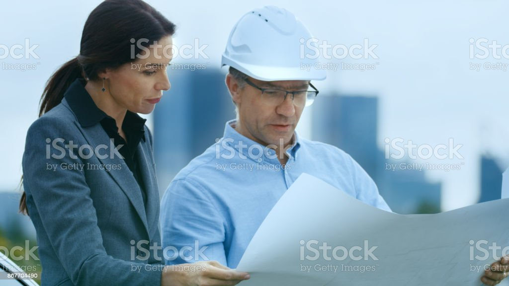 Chief Engineer Shows Project Drafts To Business Woman Investor. In the Background City with Skyscrapers. stock photo