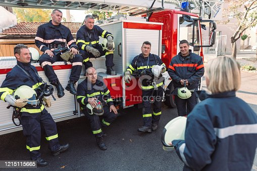 Group of male firefighters getting instructions from their female chief officer