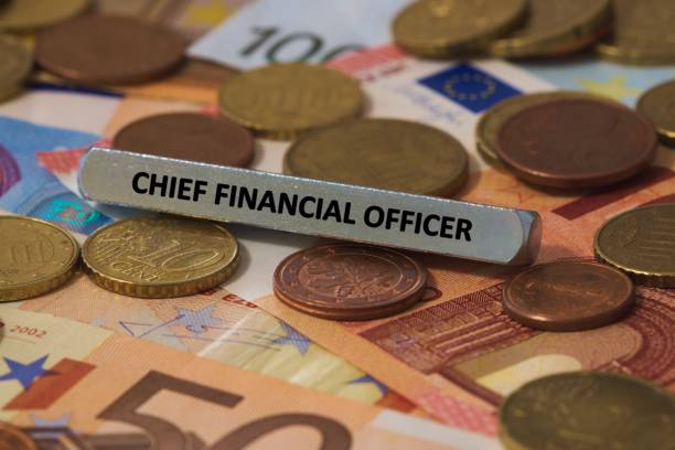 chief financial officer - the word was printed on a metal bar. the metal bar was placed on several banknotes stock photo