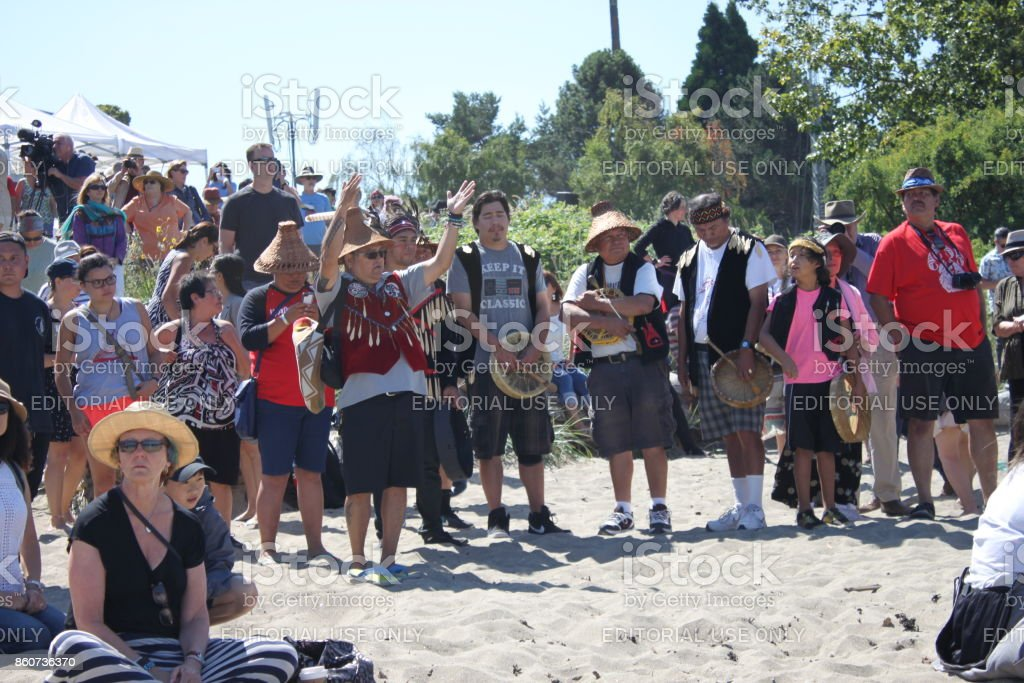 Chief greeting the canoes and guests watching canoe landing at Ambleside in West Vancouver stock photo