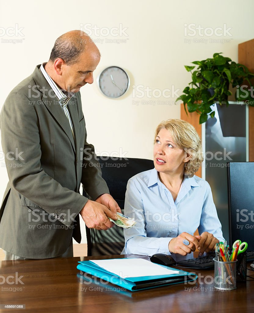 Chief paying to elderly assistant an yearly bonus stock photo