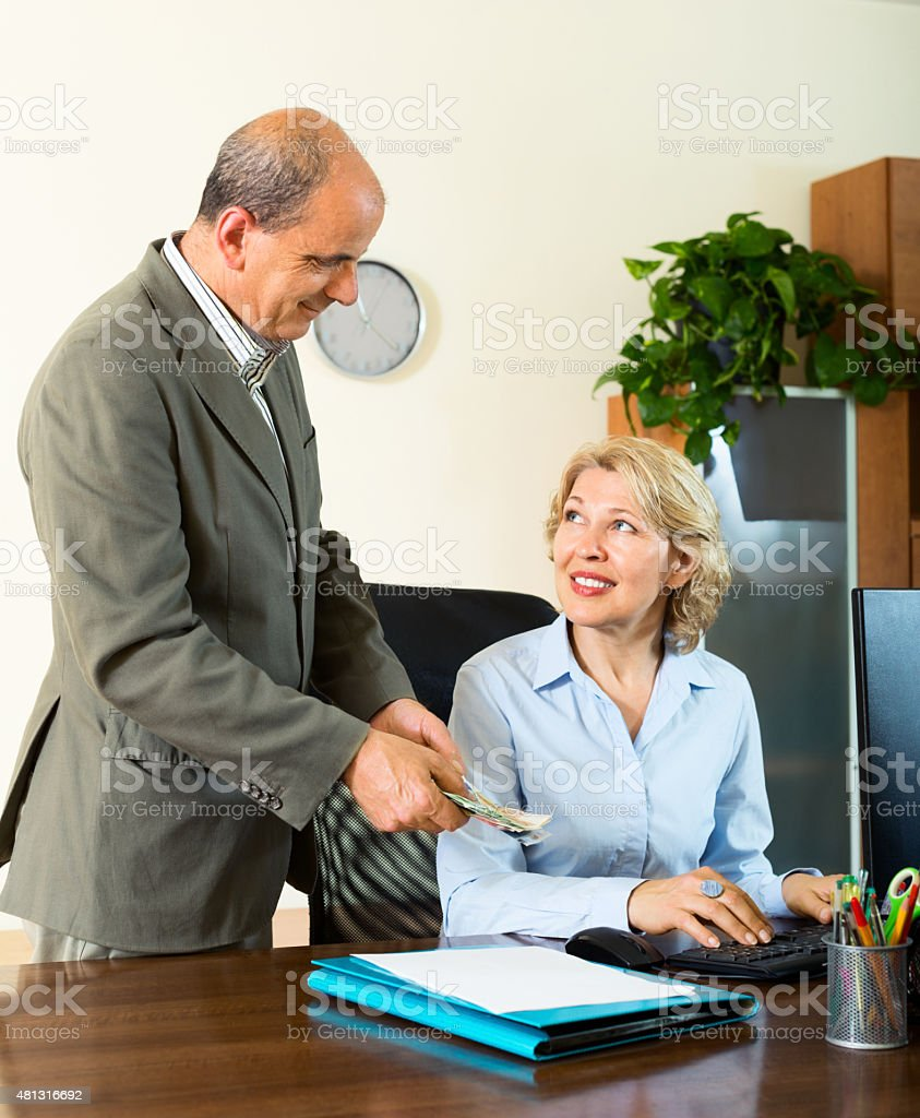 Chief paying to happy assistant an yearly bonus stock photo