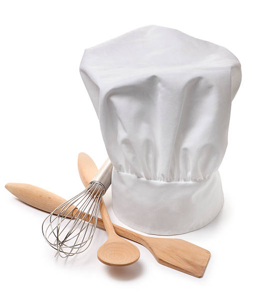 Chef A chef's hat on white with cooking utensils. Clipping path included. chef's hat stock pictures, royalty-free photos & images
