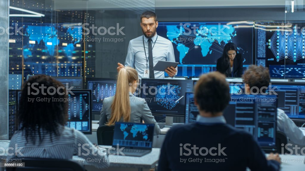 Chief Project Engineer Holds Briefing for a Team of Scientists that are Building Machine Learning System. Displays Show Working Model of Neural Network. Chief Project Engineer Holds Briefing for a Team of Scientists that are Building Machine Learning System. Displays Show Working Model of Neural Network. Administrator Stock Photo