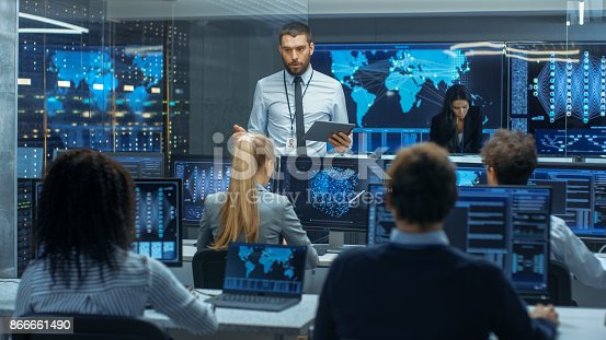 istock Chief Project Engineer Holds Briefing for a Team of Scientists that are Building Machine Learning System. Displays Show Working Model of Neural Network. 866661490