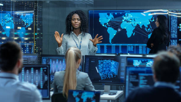 chief project engineer holds briefing for a team of scientists that are building machine learning system. displays show working model of neural network. - women in tech stock photos and pictures