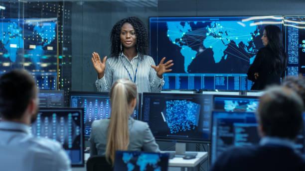 jefe proyecto ingeniero sostiene reunión de información para un equipo de científicos que son sistema de aprendizaje de máquina de construcción. las pantallas muestran el modelo de redes neuronales de funcionamiento. - clase de ciencias fotografías e imágenes de stock