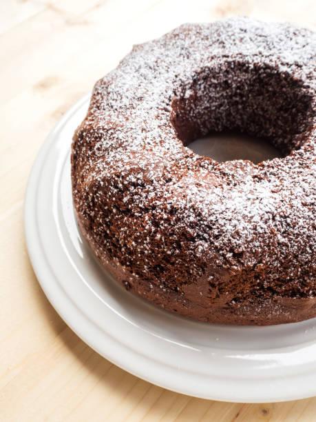 chiffon schokoladenkuchen auf weißen teller. über holztisch. einfache kuchen mit staubzucker richtfest. - schokoladen biskuitkuchen stock-fotos und bilder