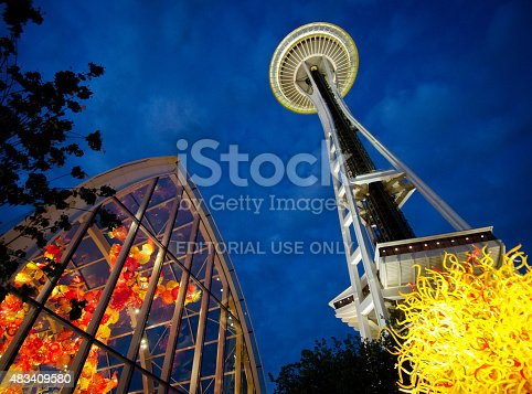 Seattle, WA, USA  - June 2, 2014: The Chihuly Garden and Glass exhibit illuminates the night as the world famous Space Needle towers above.  The exhibit in the Seattle Center showcases the artwork of Dale Chihuly and opened in 2012.