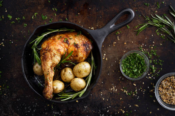 Chiken leg and potatoes in a skillet stock photo