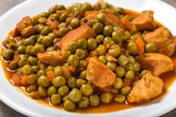 Chiken stew with peas, carrot and tomato sauce on plate stock photo