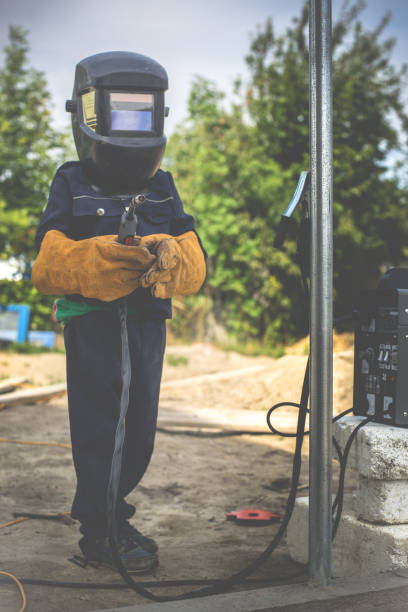 A child, a boy pretends to weld a fence. Welder's costume, gloves, mask.