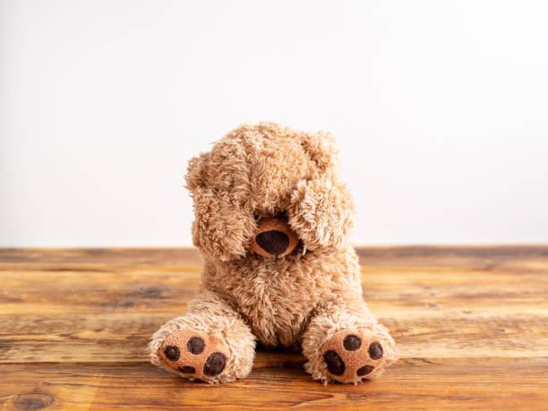 kindesmissbrauch. teddy bär hält sich die augen zu. - child abuse stock pictures, royalty-free photos & images