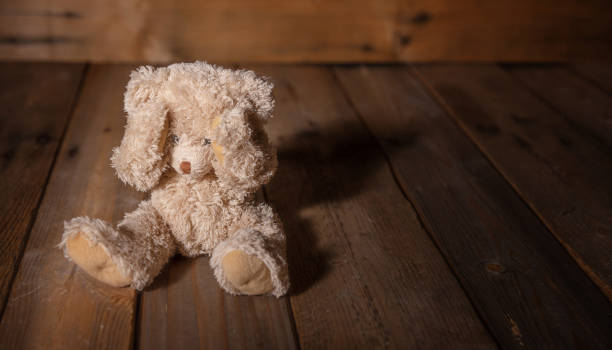 child abuse.teddy bear covering eyes, dark empty background, copy space - child abuse stock pictures, royalty-free photos & images