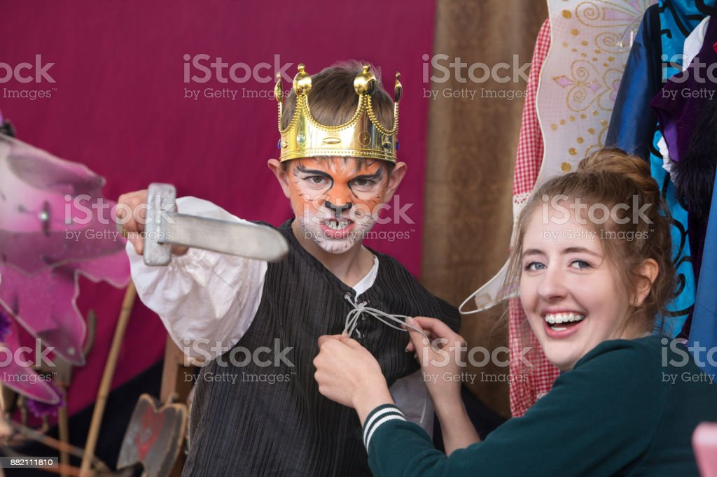 Child actor dressed as king wearing crown stock photo