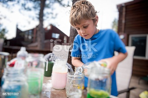 child experiments with chemicals and liquid outside