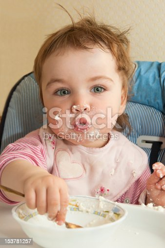 Small child tries adopts food by itself. Holds a spoon in a hand.