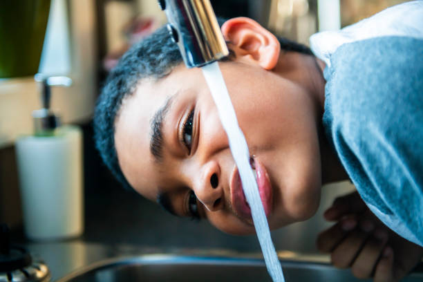 child afro american boy take water on his mouth and drink in a kitchen. stock photo