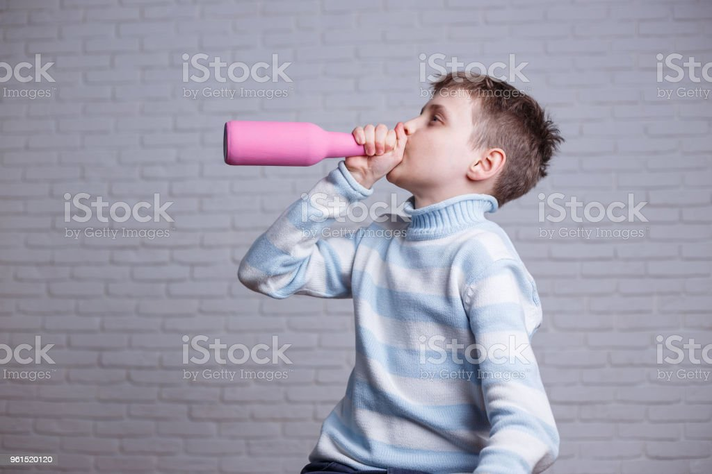 Child alcoholism. Boy drinking alcohol from a pink bottle. Hidin stock photo
