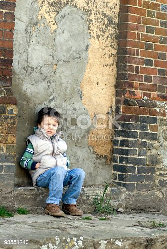 young boy sat by a stone door with hands in pockets.