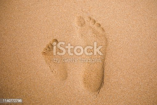 istock child and adult footprints on sand beach 1140772795